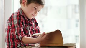 Chłopiec podrzuca strony, małe dziecko jest ubranym koszulowego obsiadanie na okno z starą książką w pomarańcze pokrywie zdjęcie wideo