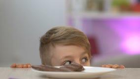 Chłopiec pojawiać się spod stołowego i kraść kawałka czekoladowy bar, ząb zdjęcie wideo