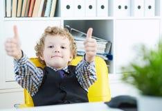 Chłopiec pokazuje kciuk w górę patrzeć w kamerę Chłopiec siedzi w szefa ` s krześle w biurze zdjęcia stock