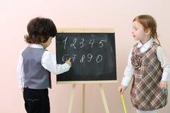 Chłopiec pokazuje palcowymi postaciami przy chalkboard dla ślicznej dziewczyny Obrazy Royalty Free