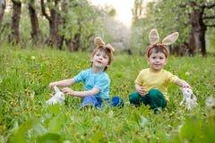 Chłopiec polowanie dla Easter jajka w wiosna ogródzie na dniu śliczny Obraz Royalty Free