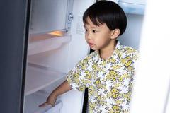 Chłopiec pomaga jego macierzystemu pracować w domu i podnosi w górę wody od fridge jego mama obrazy stock