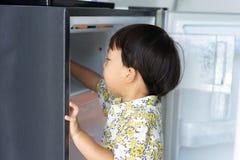 Chłopiec pomaga jego macierzystemu pracować w domu i podnosi w górę wody od fridge jego mama obraz stock