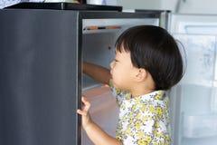 Chłopiec pomaga jego macierzystemu pracować w domu i podnosi w górę wody od fridge jego mama zdjęcia royalty free