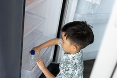 Chłopiec pomaga jego macierzystemu pracować w domu i podnosi w górę wody od fridge jego mama zdjęcie stock
