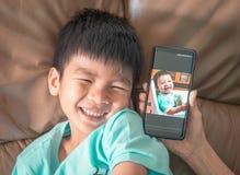 Chłopiec porównuje z jego swój dziecko obrazkiem zdjęcia royalty free