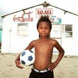 Chłopiec pozuje z piłką w społeczności miejskiej, Południowa Afryka Zdjęcia Royalty Free