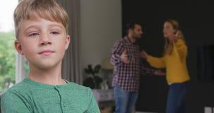 Chłopiec pozycja podczas gdy rodzice dyskutuje z each inny w tle 4k w domu zdjęcie wideo