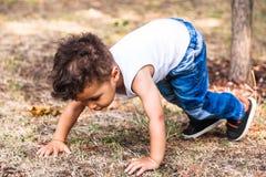 Chłopiec próba kłaść na trawie w parku dla zabawy zdjęcia royalty free