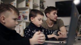 Chłopiec próbuje pisać na maszynie coś na laptop klawiaturze Uczący się dlaczego używać gadżety Programować klasę dla dzieciaków zdjęcie wideo