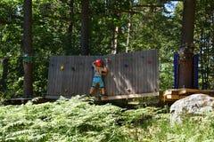 Chłopiec próbuje podbijać ścienną wspinaczkową przeszkodę fotografia royalty free