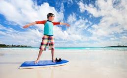 Chłopiec praktyki surfing przy plażą Zdjęcia Stock