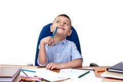 Chłopiec preschool wiek siedzi przy ołówkowym stołem w jego rękach i patrzeje zamyślenie upwards fotografia stock