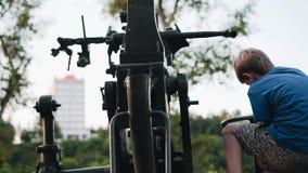 Chłopiec produkuje dążącej przeciwlotniczej instalacji Chłopiec siedzi na kontrolnej platformie Wielki plan zbiory wideo