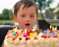 Chłopiec przed urodzinowym tortem obrazy stock