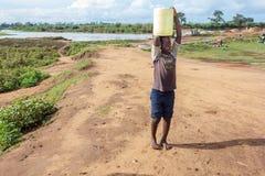 Chłopiec przewożenia woda pitna Fotografia Stock