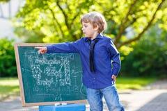 Chłopiec przy blackboard uczenie pisać Obrazy Stock