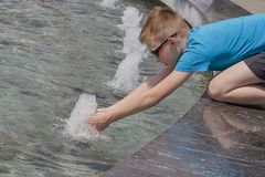 Chłopiec przy fontanną w mieście w gorącej pogodzie fotografia royalty free