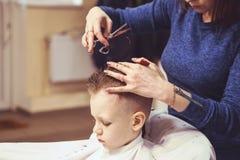 Chłopiec przy fryzjerem Dziecko okalecza ostrzyżenia hairball obraz stock