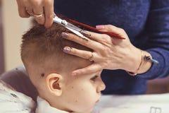 Chłopiec przy fryzjerem Dziecko okalecza ostrzyżenia hairball obrazy stock