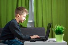 Chłopiec przy laptopem bawić się gry lub ogląda wideo, Pojęcie nałóg gry komputerowe, zamazany wzrok, okręg umysłowy obrazy royalty free