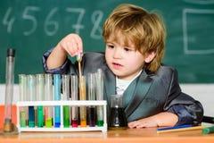 Chłopiec przy lekcją tylna szko?y Chłopiec przy szkołą podstawową szkolna dzieciaka naukowa studiowania nauka troch? zdjęcie royalty free