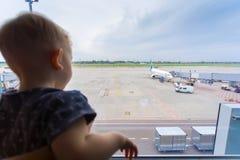 Chłopiec przy lotniskowym przyglądającym okno przy samolotem out fotografia royalty free