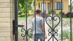 Chłopiec przybycia dom, otwarcie, zamyka bramę, jard, lato zdjęcie wideo