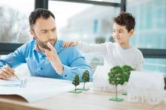 Chłopiec przyciąga ojciec uwagę podczas gdy on pracuje Obrazy Royalty Free