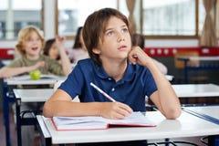 Chłopiec Przyglądająca Up Podczas gdy Pisać Przy biurkiem Zdjęcia Stock
