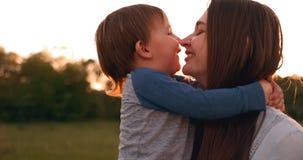 Chłopiec przytulenia matka przy zmierzchem w lecie, kochającym synu i szczęśliwym rodzinnym macaniu, zbiory