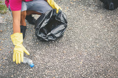 Chłopiec ręka w żółtych rękawiczkach podnosi up pustego butelka klingeryt w kosz torbę fotografia royalty free