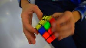 Chłopiec ręki rozwiązuje rubik sześcian zdjęcie wideo