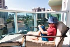 Chłopiec relaksuje na balkonie hotelowy patrzeje pejzaż miejski fotografia stock