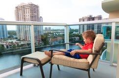 Chłopiec relaksuje na balkonie hotelowy patrzeje pejzaż miejski obrazy stock