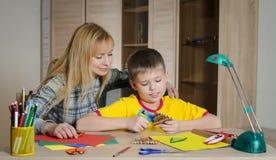 Chłopiec robi Bożenarodzeniowym dekoracjom z jego matki Robi boże narodzenie dekoraci z twój swój rękami fotografia royalty free