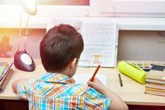 Chłopiec robi jego pracie domowej przy stołem fotografia royalty free