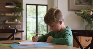 Chłopiec robi jego pracie domowej przy stołem w domowym 4k zbiory