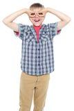 Chłopiec robi próbnym widowiskom z jego rękami Zdjęcie Royalty Free