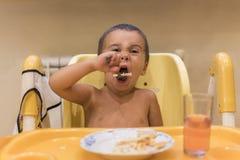 Chłopiec 2 roku jeść Children& x27; s stół Pojęcie child& x27; s niezależność Śliczna berbeć chłopiec z łyżką jest fotografia stock