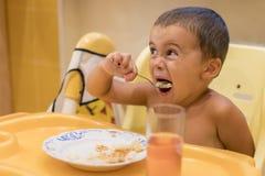 Chłopiec 2 roku jeść Children& x27; s stół Pojęcie child& x27; s niezależność Śliczna berbeć chłopiec z łyżką jest zdjęcia royalty free