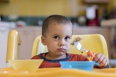 Chłopiec 2 roku je mięso Children& x27; s stół Pojęcie child& x27; s niezależność śmieszny dzieciak w dziecka siedzeniu obraz stock