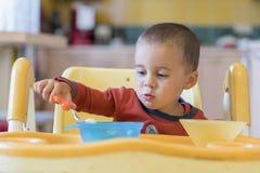 Chłopiec 2 roku je mięso Children& x27; s stół Pojęcie child& x27; s niezależność śmieszny dzieciak w dziecka siedzeniu zdjęcia stock