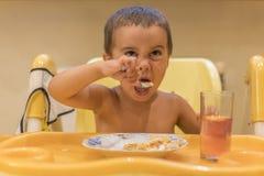 Chłopiec 2 roku je owsiankę Children& x27; s stół Pojęcie child& x27; s niezależność Śliczna berbeć chłopiec z łyżką jest zdjęcie royalty free