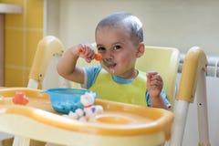 Chłopiec 2 roku je owsiankę Children& x27; s stół Pojęcie child& x27; s niezależność śmieszny dzieciak w dziecka siedzeniu obrazy royalty free