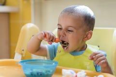 Chłopiec 2 roku je owsiankę Children& x27; s stół Pojęcie child& x27; s niezależność śmieszny dzieciak w dziecka siedzeniu obraz stock
