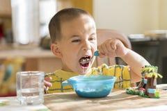 Chłopiec 4 roku je owsiankę Children& x27; s stół Pojęcie child& x27; s niezależność chłopiec breakfasting z obraz royalty free
