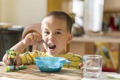 Chłopiec 4 roku je owsiankę Children& x27; s stół Pojęcie child& x27; s niezależność chłopiec breakfasting z zdjęcia stock