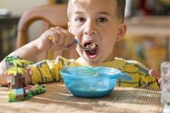 Chłopiec 4 roku je owsiankę Children& x27; s stół Pojęcie child& x27; s niezależność chłopiec breakfasting z zdjęcia royalty free