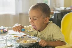Chłopiec 2 roku je owsiankę Children& x27; s stół Pojęcie child& x27; s niezależność szczęśliwy chłopiec łasowanie zdjęcie royalty free